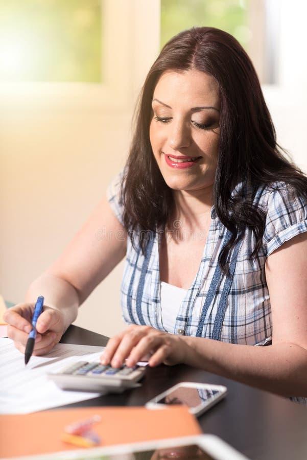 Ung kvinnlig revisor som använder räknemaskinen arkivfoton