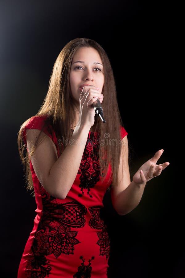 Ung kvinnlig sångare i röd klänning arkivbilder