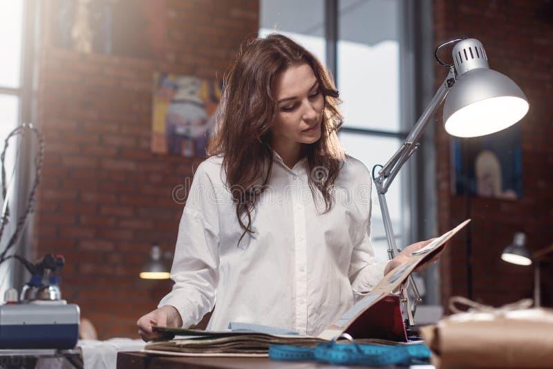 Ung kvinnlig sömmerska som väljer material från katalog i studio Anpassa att se till och med tyger, medan stå i a royaltyfri bild