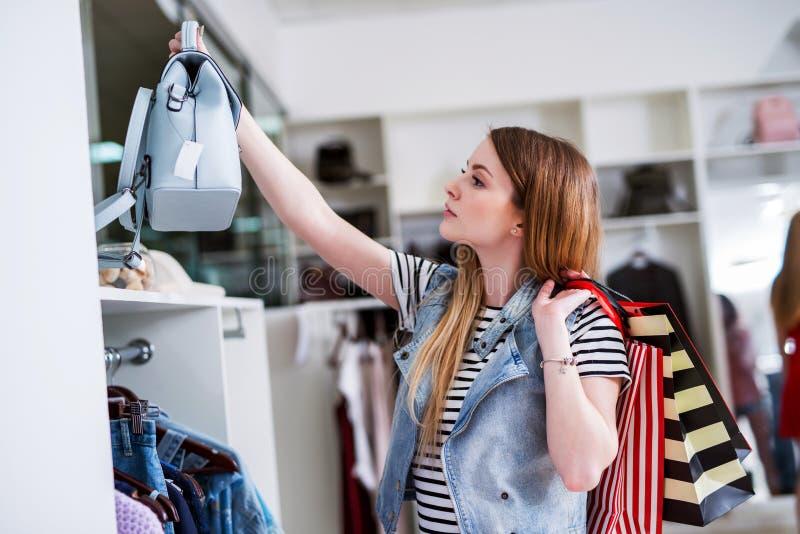 Ung kvinnlig shoppare med shoppingpåsar som väljer handväskan som matchar hennes tillfälliga stil royaltyfri bild