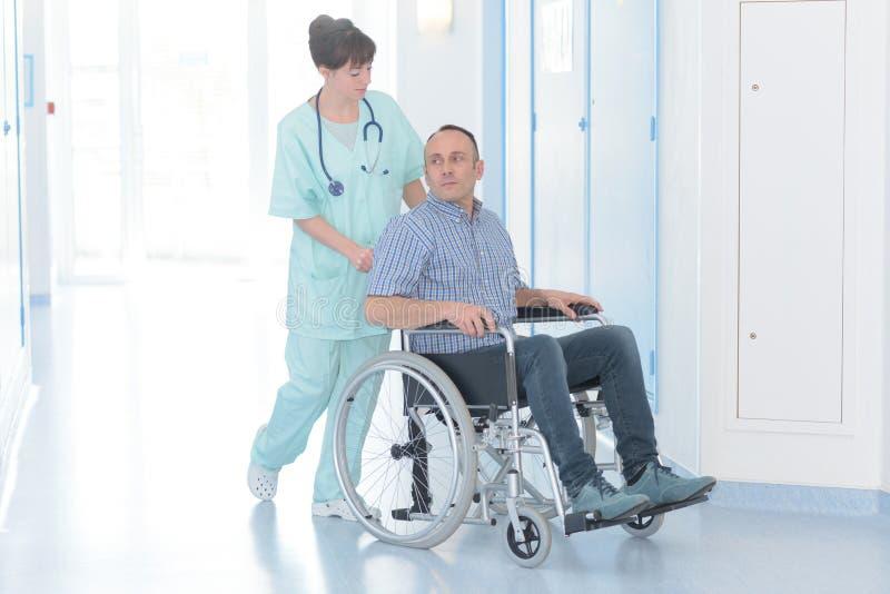 Ung kvinnlig sjuksköterska med den rörelsehindrade manliga patienten på rullstolen arkivfoton