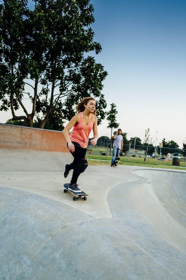 Ung kvinnlig skateboarder på skateparken arkivbild