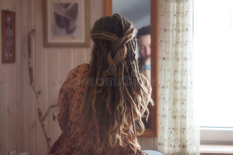 Ung kvinnlig som är främst av spegeln i sovrum arkivbilder