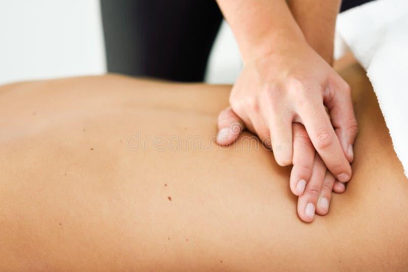 Ung kvinnlig som mottar en koppla av tillbaka massage i en brunnsortmitt arkivfoton