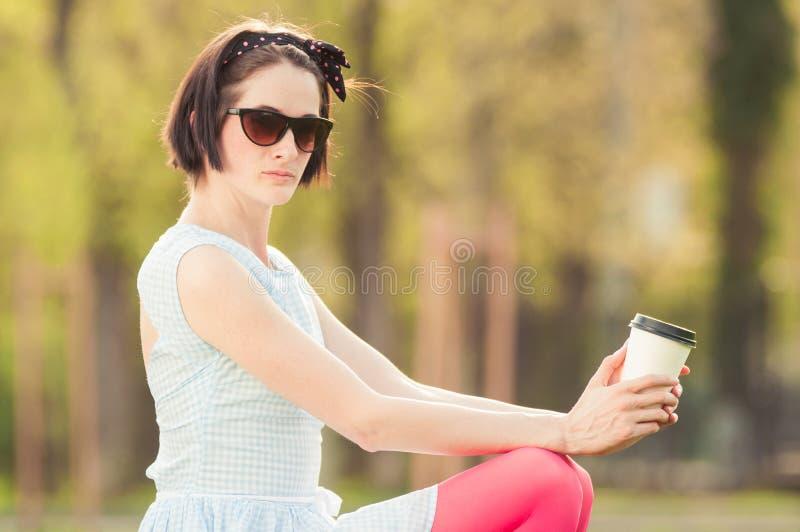 Ung kvinnlig som tycker om en ny kopp kaffe i närbild arkivfoto