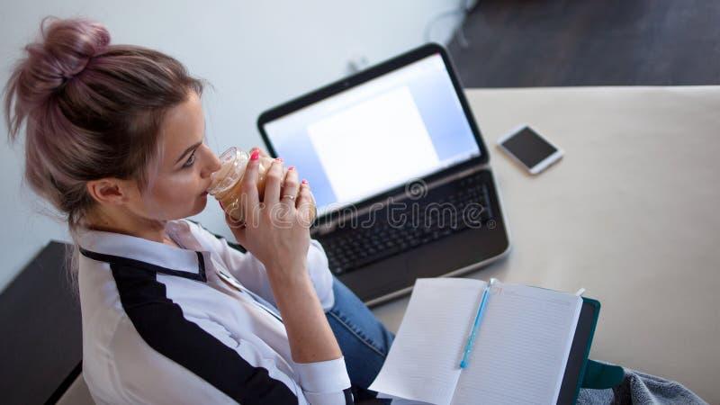 Ung kvinnlig student eller entreprenör som hemifrån arbetar Avlägset arbete arkivbilder