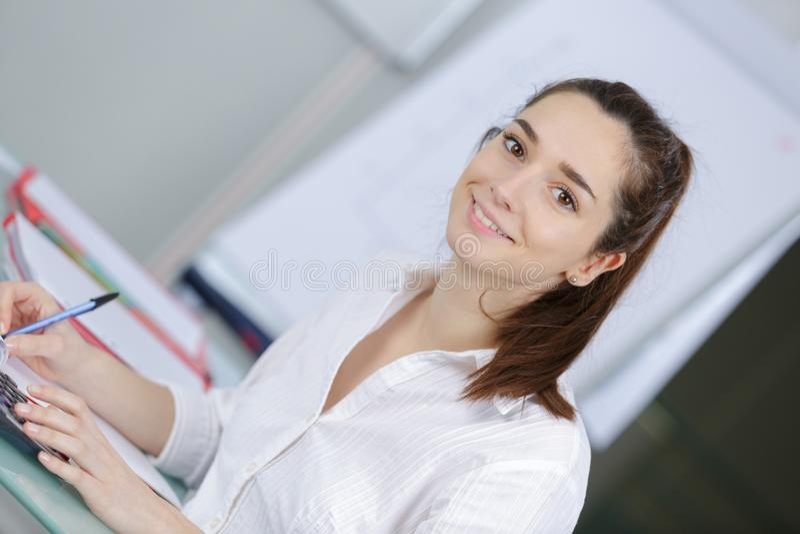 Ung kvinnlig student på universitetklassrumet royaltyfri fotografi