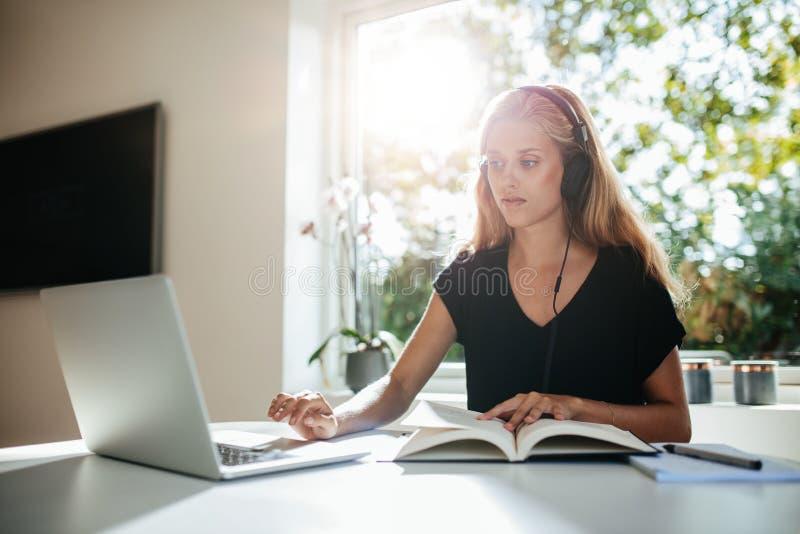 Ung kvinnlig student som hemma studerar arkivbilder
