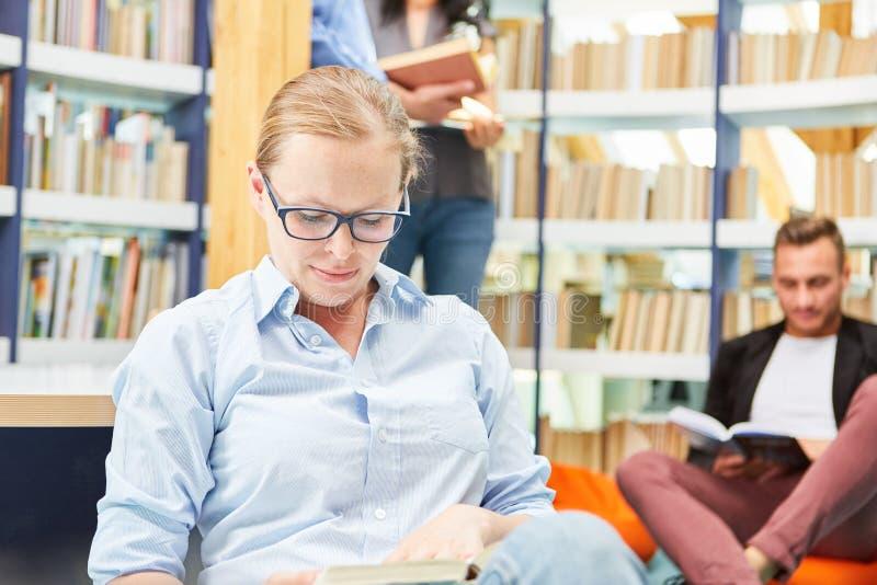Ung kvinnlig student som läser boken i arkivet fotografering för bildbyråer