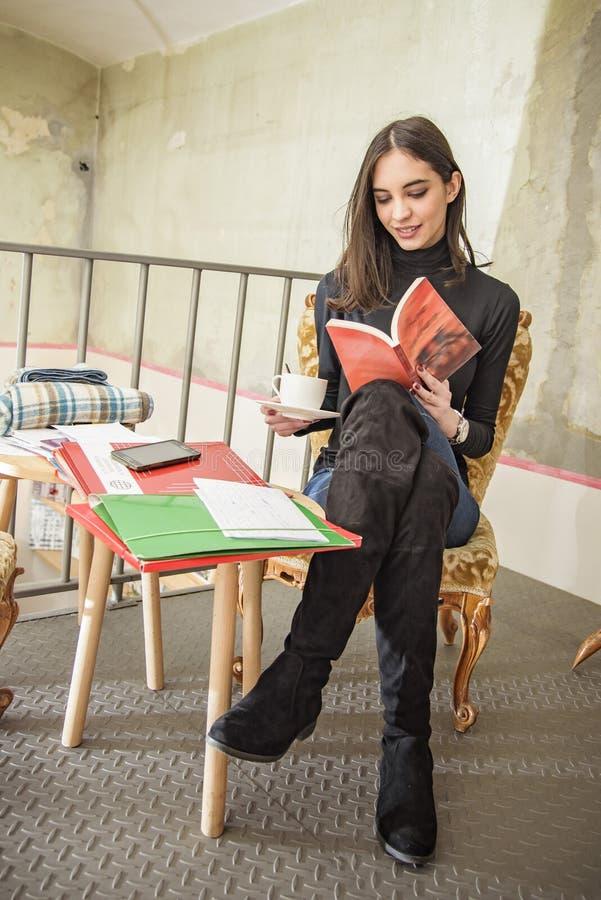 Ung kvinnlig student som läser en bok i ett kafé arkivfoto