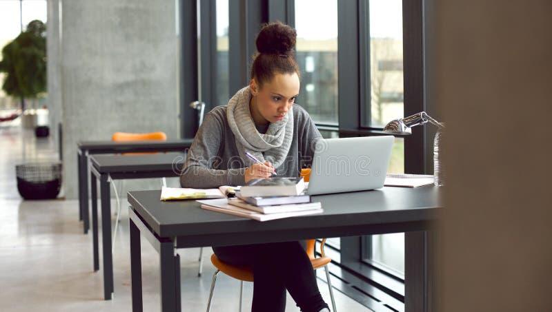 Ung kvinnlig student som tar anmärkningar för henne studien royaltyfri bild