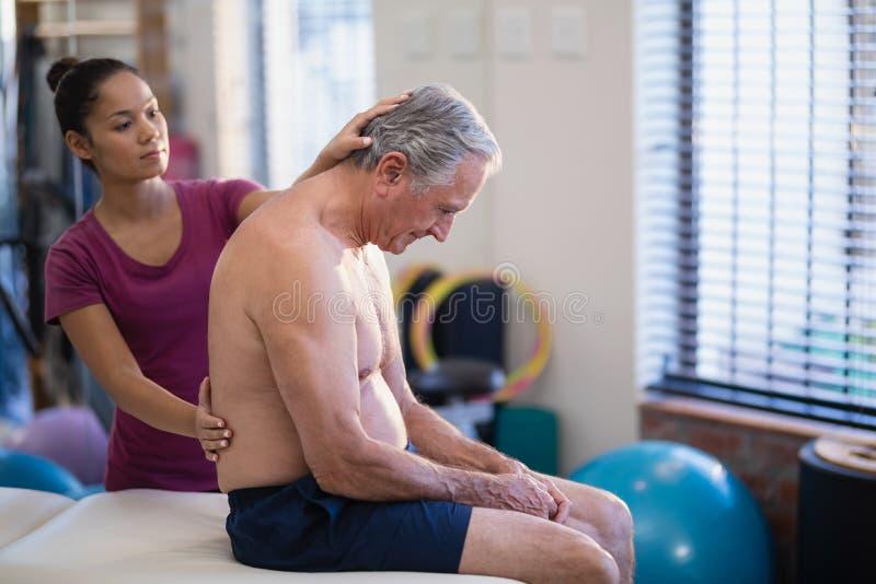 Ung kvinnlig terapeut som tillbaka ger massage till högt manligt tålmodigt sammanträde på säng royaltyfri fotografi