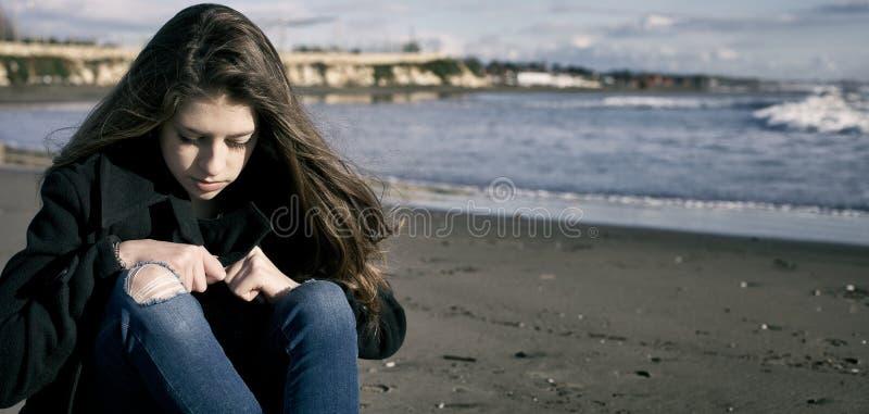 Ung kvinnlig tonåring framme av stormen på den ledsna stranden royaltyfri fotografi