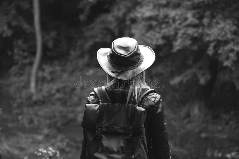Ung kvinnlig turist med en hatt för ryggsäck- och lädercowboystil som ser avståndet kopiera avst?nd f?r din text _ arkivfoto