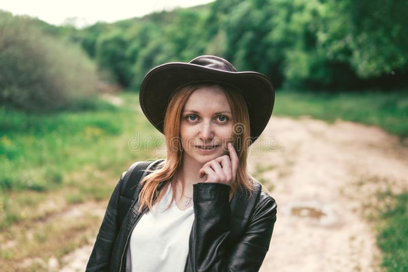 Ung kvinnlig turist med en rosa hatt för ryggsäck- och lädercowboystil som ser avståndet kopiera avst?nd f?r din text fotografering för bildbyråer