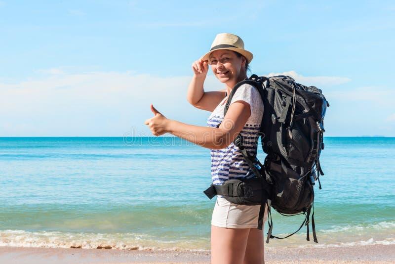 Ung kvinnlig turist med en ryggsäck som är lycklig på stranden royaltyfria foton
