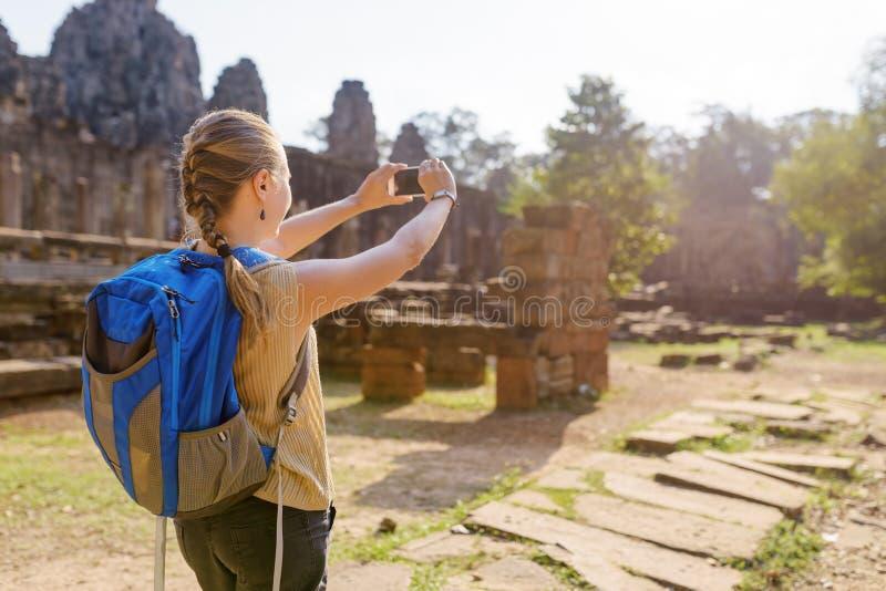 Ung kvinnlig turist med smartphonen i Angkor Thom royaltyfri fotografi
