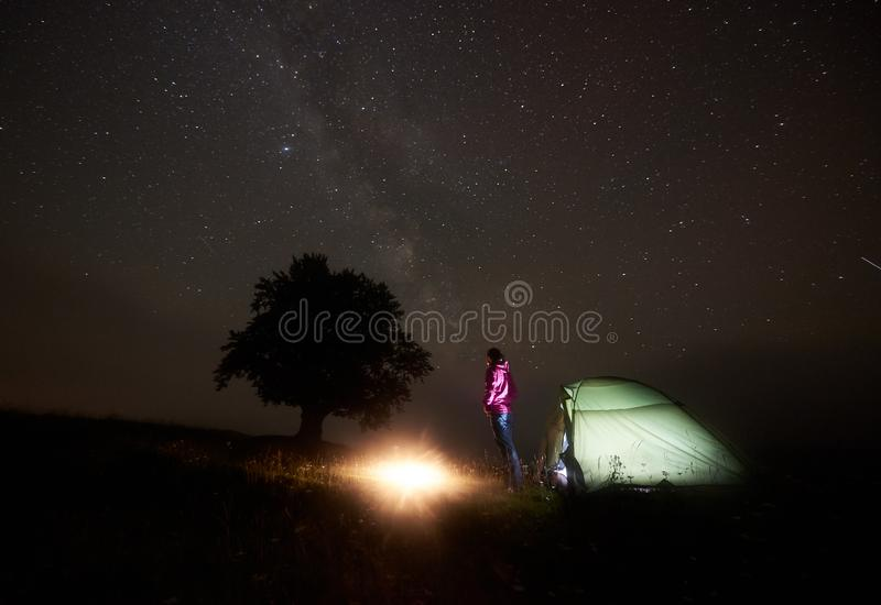 Ung kvinnlig turist som vilar nära det upplysta tältet som campar i berg på natten under stjärnklar himmel royaltyfria bilder