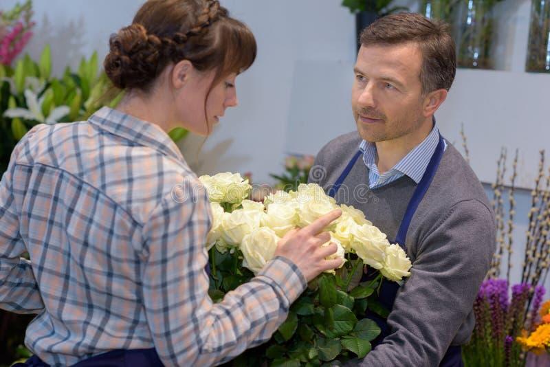 Ung kvinnlig väljande höger blomma för manlig blomsterhandlareportion royaltyfri foto