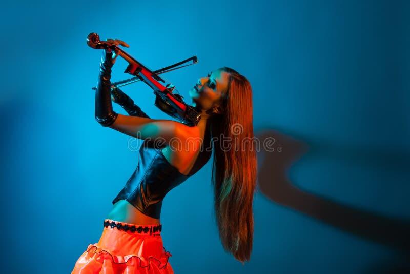Ung kvinnlig violinist som spelar fiolen royaltyfri fotografi