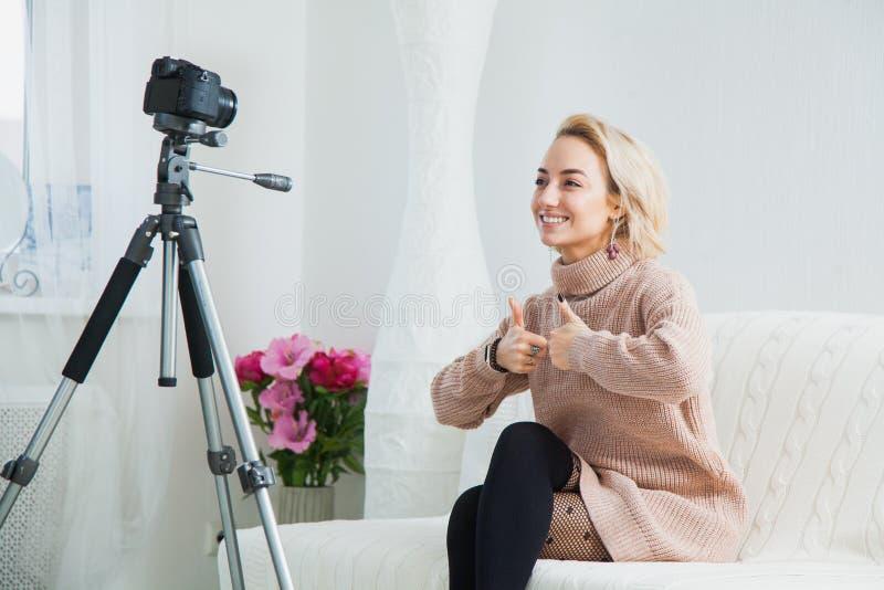 Ung kvinnlig vlogger bredvid kamera hemma inspelningvideo för blogg fotografering för bildbyråer
