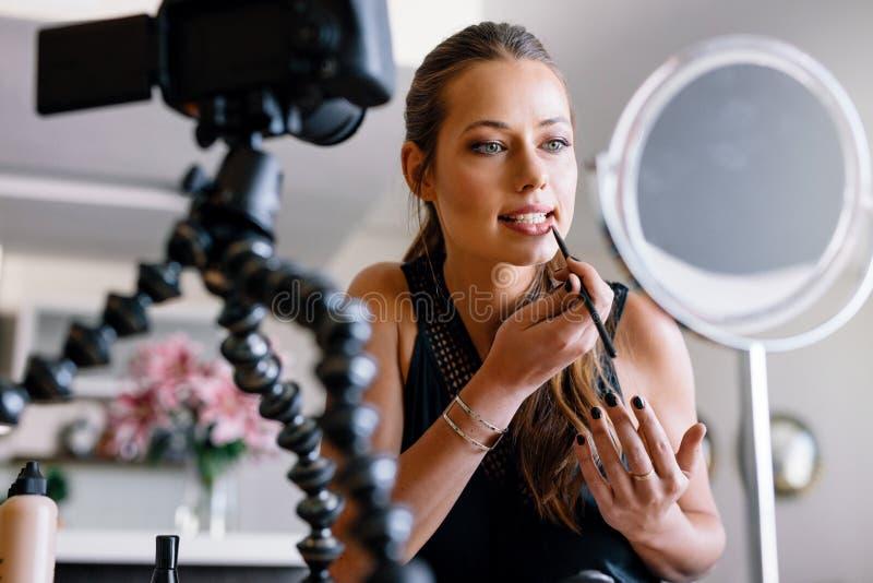 Ung kvinnlig vlogger som antecknar en sminkvideo för hennes vlog royaltyfri bild