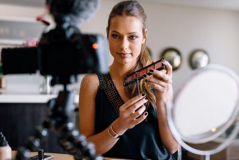 Ung kvinnlig vlogger som antecknar en sminkvideo för hennes vlog fotografering för bildbyråer