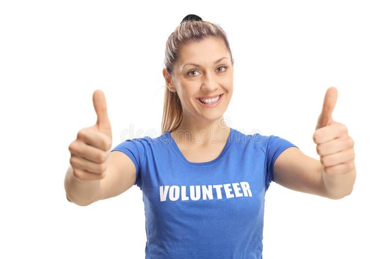 Ung kvinnlig volontär som visar upp tummar och ler på kameran royaltyfria bilder