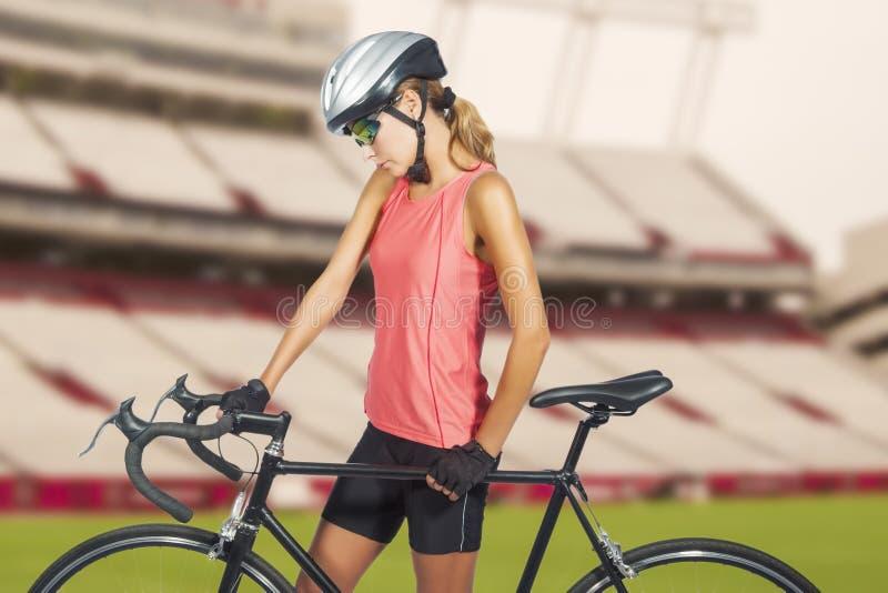 Ung kvinnlig yrkesmässig cykla idrottsman nen som poserar med tävlings- bik royaltyfri foto