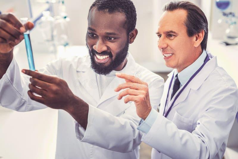 Ung läkare som ler, medan rymma provröret royaltyfria bilder