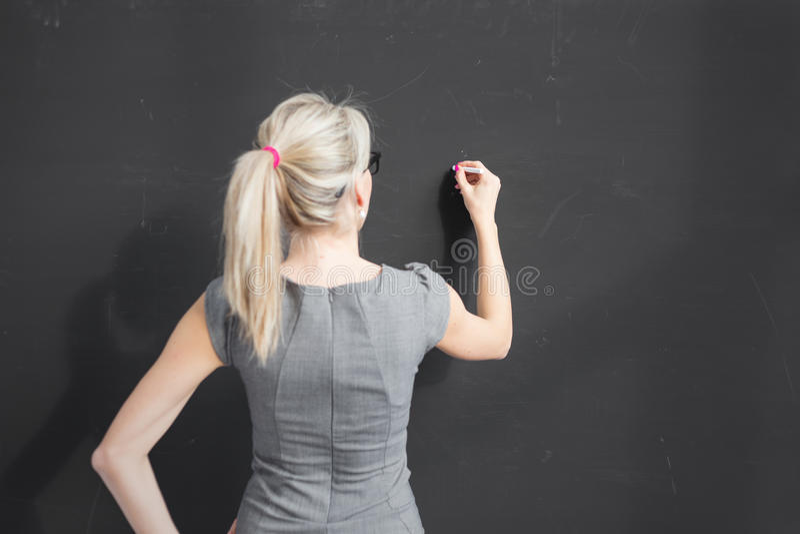Ung lärarehandstil med vit krita på den tomma svart tavla i klassrum royaltyfria foton