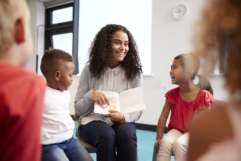Ung lärarinna som visar en bild i en bok till barn i en grupp för begynnande skola som sitter på stolar i klassrumet, över som är royaltyfri bild