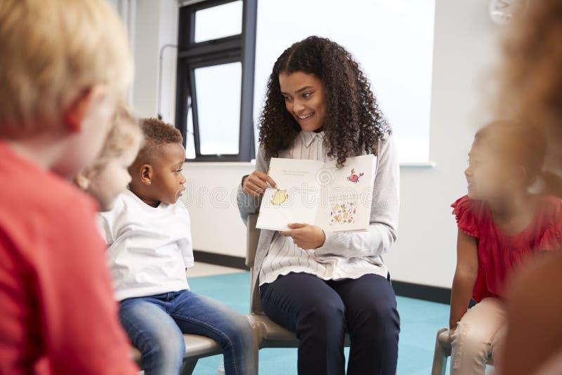 Ung lärarinna som visar en bild i en bok till dagisbarn som sitter på stolar i en cirkel i klassrumet, slut upp royaltyfria foton