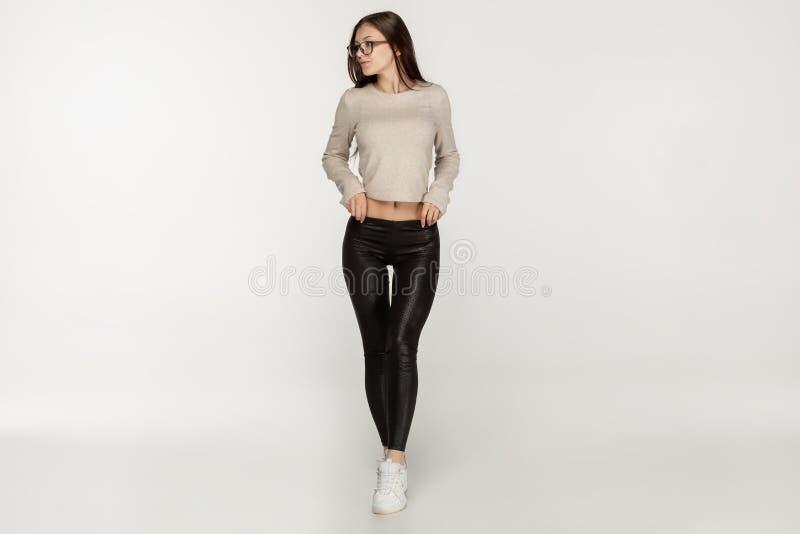Ung lång haired brunettflicka i solglasögon som bär svarta legginds royaltyfri fotografi