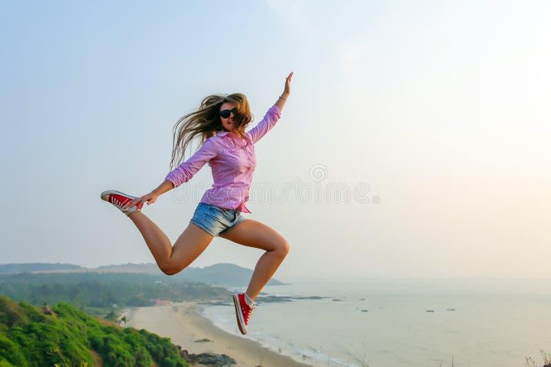 Ung långhårig flicka i kortslutningar och röda gymnastikskohopp som är höga på bakgrunden av det stunningly härliga landskapet me arkivbilder