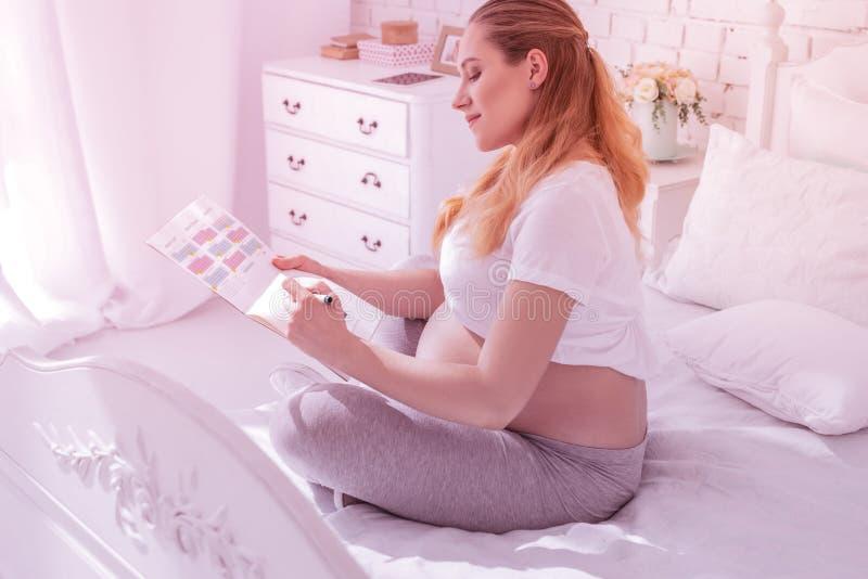Ung långhårig gravid kvinna i en vit t-skjorta som markerar data i kalendern royaltyfria bilder