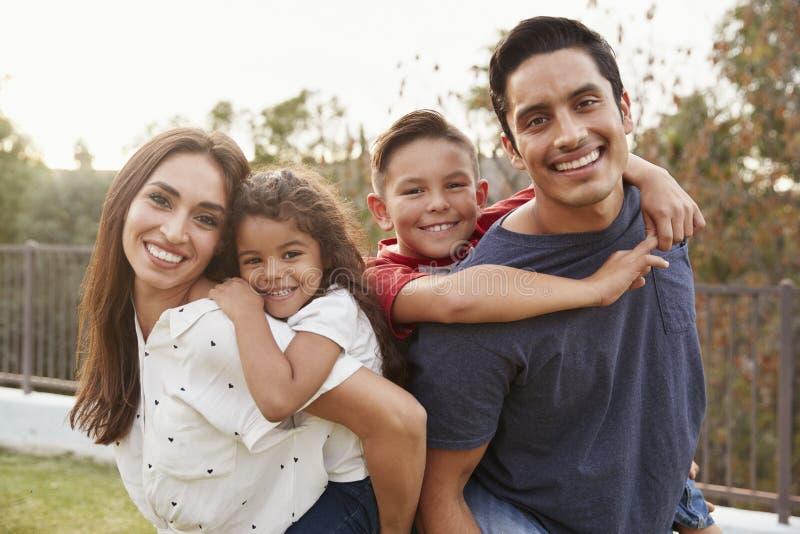 Ung latinamerikansk förälderridtur på axlarna som deras barn i parkerar och att le till kameran, fokus på förgrund arkivfoton
