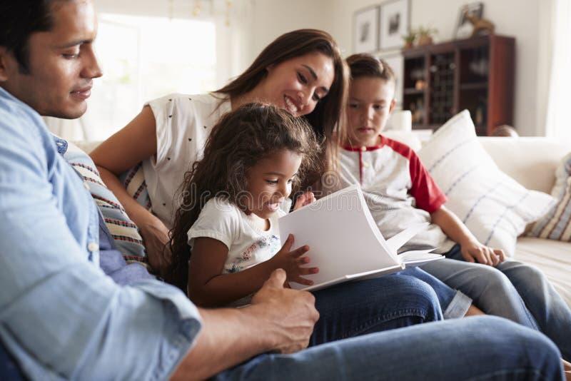 Ung latinamerikansk familj av fyra som tillsammans sitter på soffaläseboken i deras vardagsrum royaltyfri fotografi