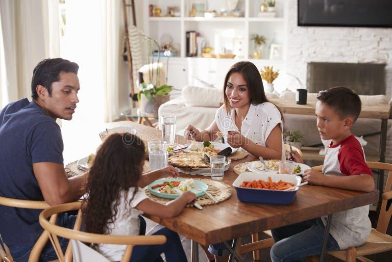Ung latinamerikansk familj som sitter på den äta middag tabellen som tillsammans äter matställen royaltyfri fotografi
