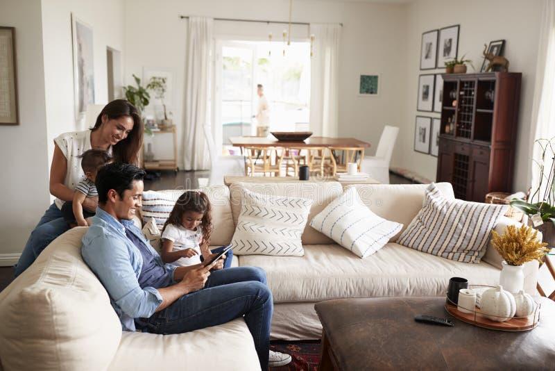 Ung latinamerikansk familj som sitter på soffan som tillsammans läser en bok i deras vardagsrum royaltyfri foto