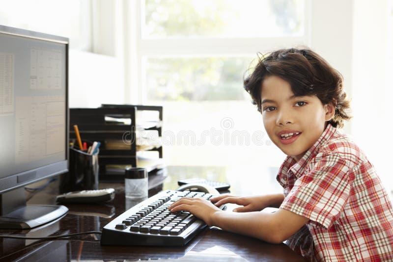 Ung latinamerikansk pojke som hemma använder datoren royaltyfri fotografi