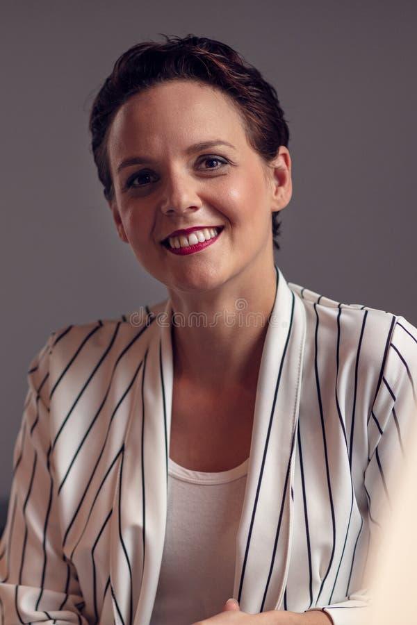 Ung le affärskvinnastående på grå bakgrund royaltyfri fotografi