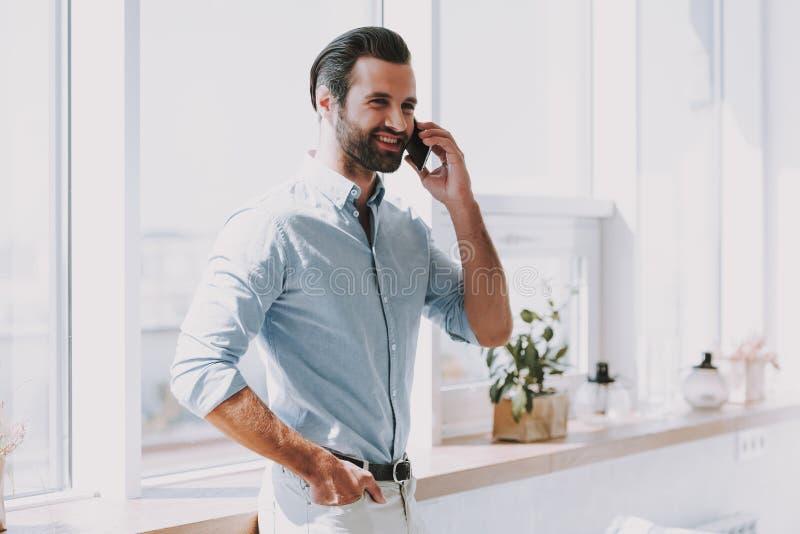 Ung le affärsman som talar på telefonen fotografering för bildbyråer