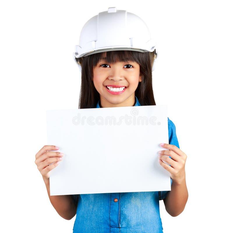 Ung le asiatisk flicka i en byggnadshjälm som rymmer ett ark av royaltyfri fotografi
