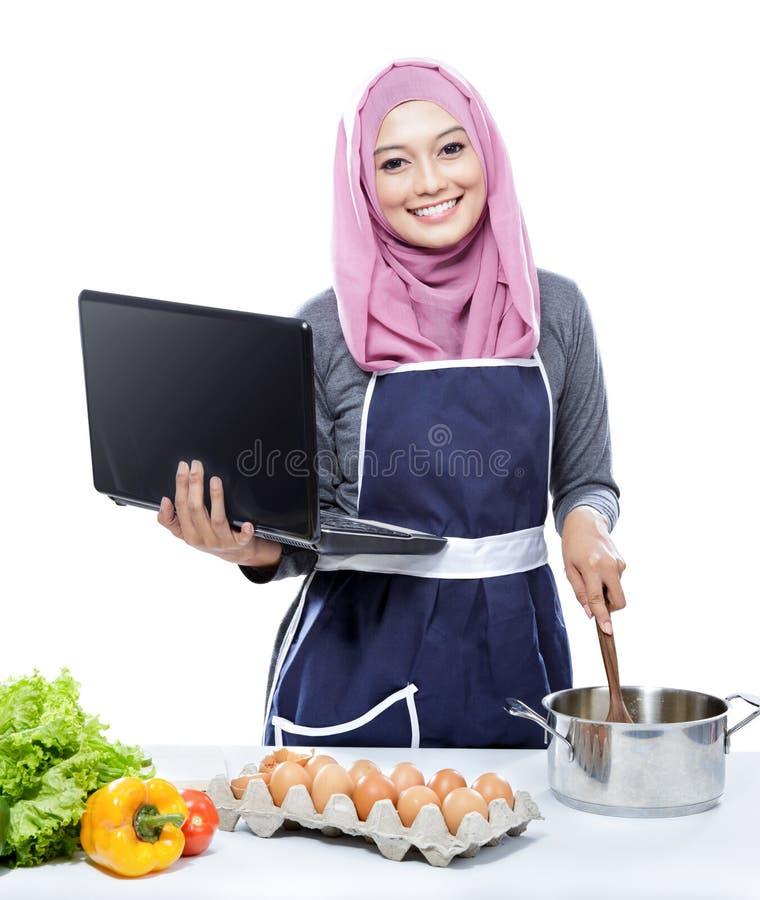 Ung le bärande hijab för kvinna på bärbar datorPC:N som lagar mat göra fo arkivbild