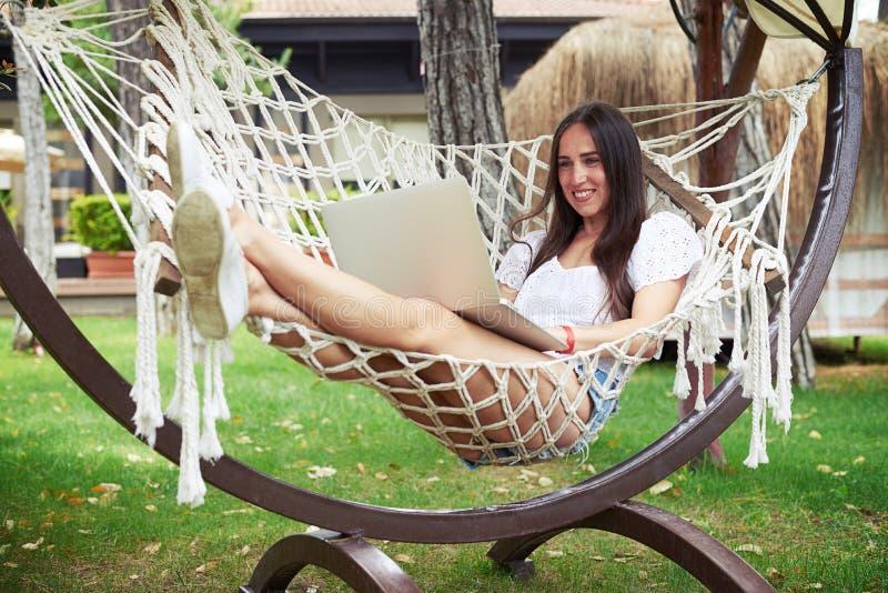 Ung le brunett i hängmatta med bärbara datorn i trädgård arkivfoto