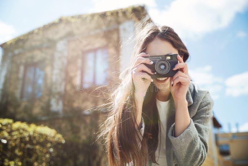 Ung le brunett som utomhus tar bilden med fotokameran royaltyfria bilder