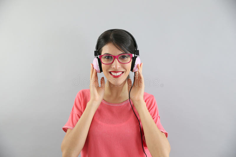 Ung le brunettkvinna med glasögon som lyssnar till musik arkivfoton