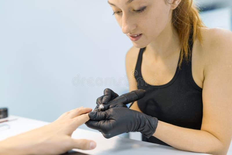 Ung le flickamanikyrist som gör yrkesmässig manikyr Spika och räcka omsorg i skönhetsalong royaltyfri bild
