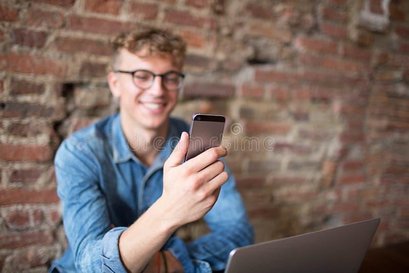 Ung le hipstergrabb som har den videopd appellen med vänner via mobiltelefonen som sitter mot tegelstenväggen med kopieringsutrym royaltyfria foton